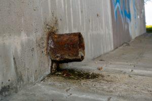 Verrostetes Rohrende, das aus einer Mauer herausragt