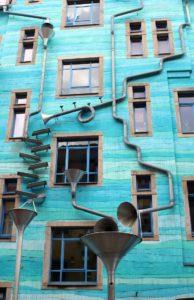 Hausfassade mit Kunstwerk aus verschieden geformten Rohren