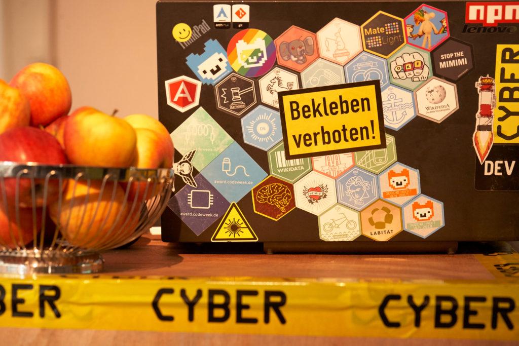 """Laptop neben Obstschale (witzig: der Laptop-Deckel ist vollgeklebt mit Stickern und ganz oben klebt der Sticker """"Bekleben verboten"""")"""