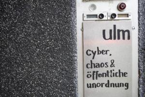 """Klingelschild mit der Beschriftung: """"Ulm - cyber, chaos und öffentliche unordnung"""""""