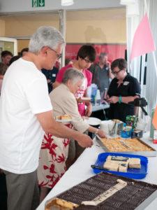 OB Czisch bekommt Kuchen von Stadträtin Helga Malischewski. Im Hintergrund Ulrike Hudelmaier vom Innovationszentrum TFU, die die AktivistInnengruppe in der Planungs-phase beraten und unterstützt hatte.