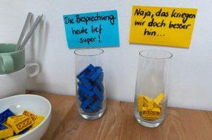 2 Gläser mit unterschiedlich vielen blauen und gelben Legosteinen gefüllt